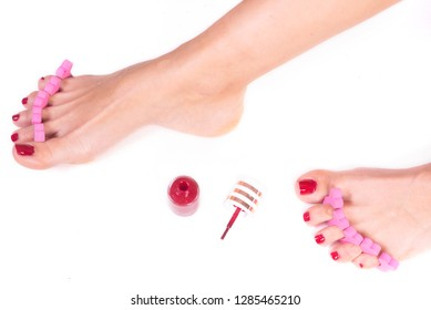 applying pedicure to woman's feet with red toenails, in pink toe separators, on white isolated background .
