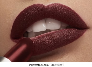 Applying red lipstick on lips in close up photo in studio lighting