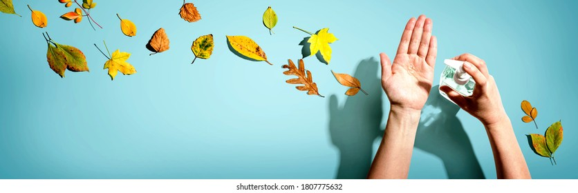 Applying sanitizer gel with autumn leaves - healthcare and hygiene concept