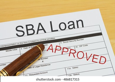 Applying for a SBA Loan Approved, SBA Loan application form with a pen on a desk with an approved stamp