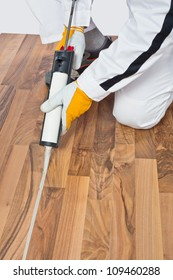 Applying silicone sealant in spaces of old wooden floor