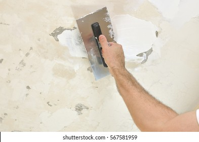 Applying spackle compound with a finishing trowel to a ceiling
