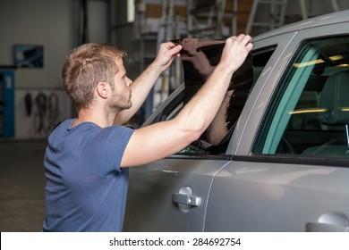 Applying tinting foil onto a car window in a workshop
