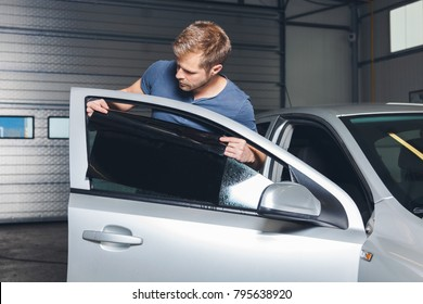Applying tinting foil onto a car window in a workshop
