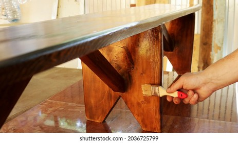 applying varnish on a wooden bench in a workshop, varnishing a wooden product by hand, manual lacquering of handmade furniture, processing with a protective varnish a bench made of wood