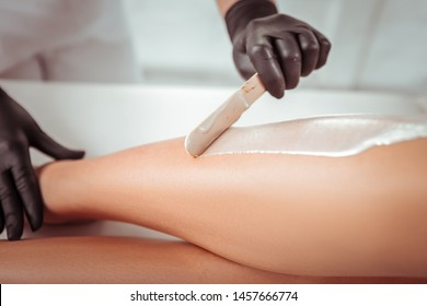 Applying warm wax. Resolute salon worker having depilation procedure and covering legs with special wax material