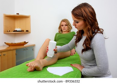 applying wax on female leg to remove hair