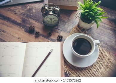 Appointment Calendar Concept.Desktop Calender, Diary, Coffee place on office desk, work online at home. Notebook for Planner plan timetable, agenda, appointment management each date, month, and year.