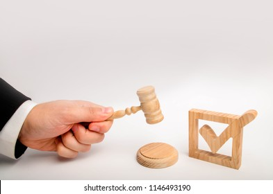 Appointment of a judge, election to a constitutional court. Control over the government elections. A wooden checkmark and a hammer of the judge on a white background. referendum and elections.