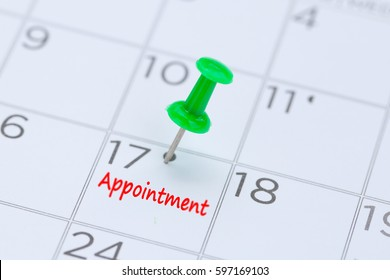 Appointment written on a calendar with a green push pin to remind you and important appointment.