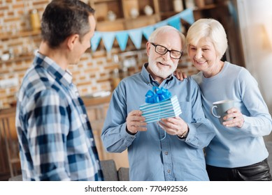 Appreciate your attention. Happy elderly man examining his birthday present, having received it from his wife and son
