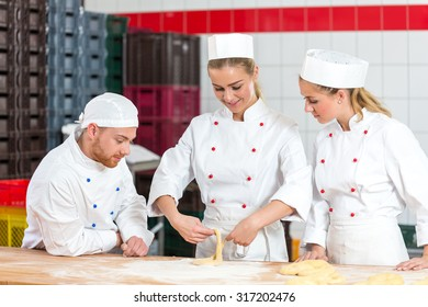 apprentice in bakery trying to make pretzels and sceptical bakers are watching