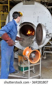 An apprentice boiler attendant cleans ash from the firebox while the extraction fan draws away smoke and fine ash particles