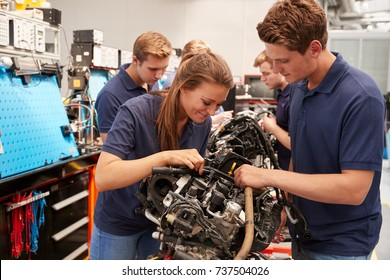 Apprentice car mechanics working on an engine