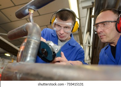 apprentice using a grinding machine