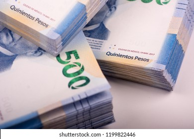 approach to 3 bundles of 500 mexican pesos bills, new design of banknotes on white background