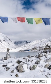 Approaching Gokyo village on the shore of a mountain lake, Everest region, Nepal. Tibetan flags and stone stacks in snow at the sides of the trail.
