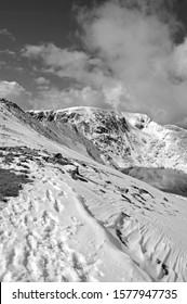 Approaching Helvellyn's Striding Edge (Lake District, Cumbria, England) on a perfect winter's day. Helvellyn's summit is in the distance and Red Tarn is prominent.