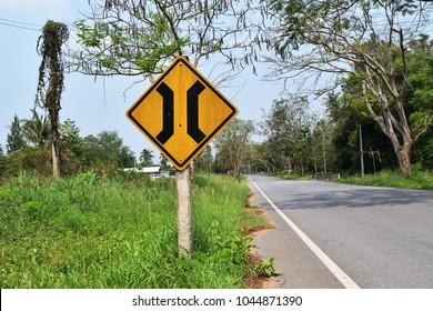 Approaching narrow bridge sign on roadside in Thailand
