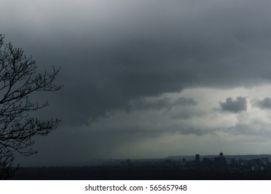 Approaching ominous storm on city skyline, large cloudscape, mist and rain or snow