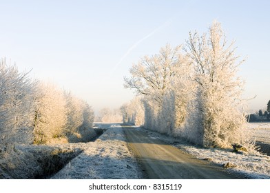 Approaching a rural intersection on a beautiful winter morning with hoarfrost covered trees