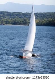 Approaching sail boat towing a dinghy in Lake Champlain near Burlington, VT