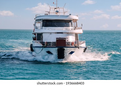 Approaching speedy passenger boat yacht cruising along turquoise sea waters in front of blue sky with white clouds