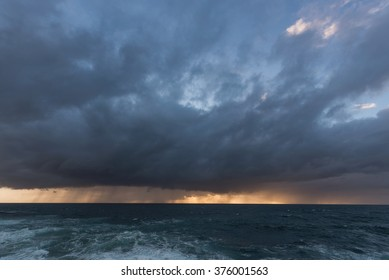 Approaching storm cloud with rain over the sea during sunrise