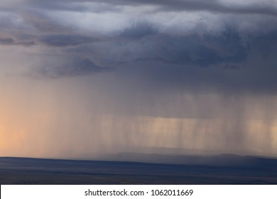 Approaching storm.  Rain falling from dark clouds in the distance.  Summer storm over the northern Arizona desert.
