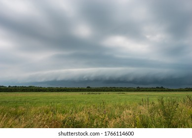Approaching thunderstorm with arcus (shelf cloud) over plain landscape
