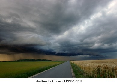Approaching thunderstorm with asphalt road leading towards it