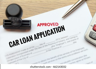Approved car loan application form lay down on wooden desk with rubber stamp and calculator.