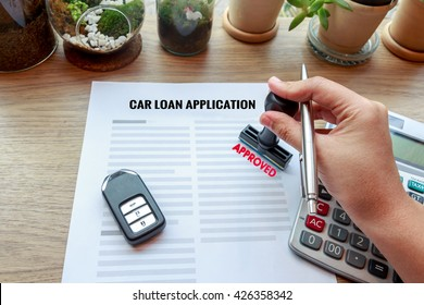Approved car loan application with car key, rubber stamp and calculator concept