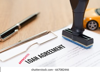 Approved loan agreement document with rubber stamp and car model toy on wooden desk