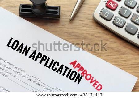 Approved loan application with rubber stamp and calculator concept
