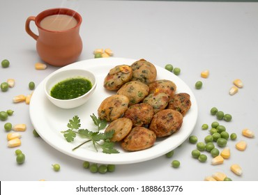 Appum or Appe, Appam or Mixed dal or Rava Appe served with green  chutney and tea. A Ball shape popular south Indian breakfast dish, Selective focus