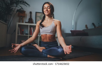appy young sportive woman meditating at home in the morning practicing yoga, Wellness concept, Woman breathing doing Ardha Padmasana exercise sitting indoor in lotus pose with mudra gesture