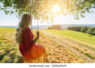 appy young woman on a swing with sunset background view and landscape
