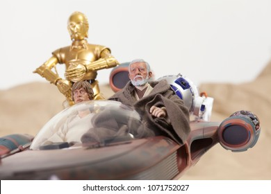 APR 17 2018: Recreation of a scene from Star Wars A New Hope; Luke Skywalker, Obi Wan 'Ben' Kenobi and the droids R2D2 and C3P0 riding in a X34 Landspeeder on Tattooine - Hasbro Black Series figures