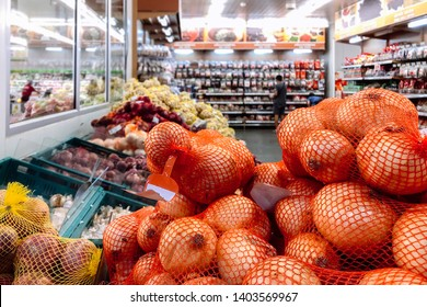 APR 30, 2019 Bangkok, Thailand - Pile of fresh onions wrapped in net mesh bag in supermaket grocery with customer chosing product from shelves in background