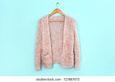 Apricot cardigan on hanger against trendy color background