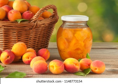 Apricot compote in a glass jar and a bunch of mature apricots in a basket on a wooden table. Sweet and healthy dessert.