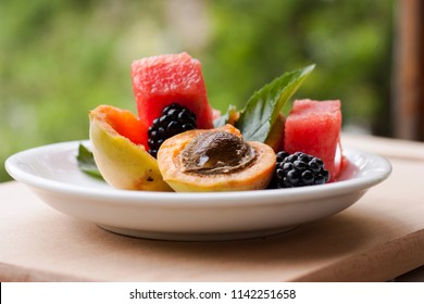 Apricot halves, slices of watermelon, blackberries, mint leaves on a white plate close-up