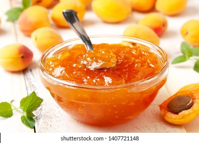 apricot jam in a glass bowl, fresh apricots on a wooden background close-up