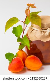 Apricot jam in a glass jar with ripe bright apricots with leaves on a white background