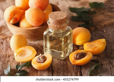 apricot kernel oil in a glass jar closeup on the table and ingredients. Horizontal