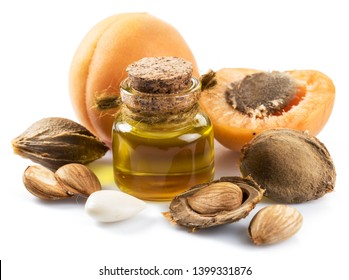 Apricot kernel oil and apricot kernels isolated on the white background.