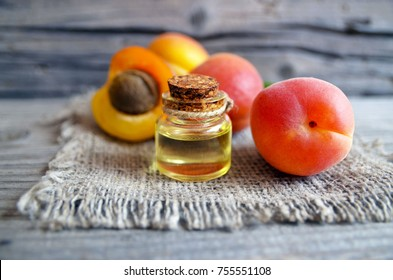Apricot oil from kernels in a glass jar and fresh ripe apricots for spa,beauty treatment,aromatherapy and bodycare on old wooden table.