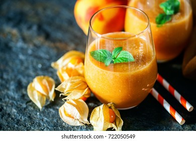 Apricot, peach and cape gooseberry cocktail on stone table . Summer concept, fresh fruits
