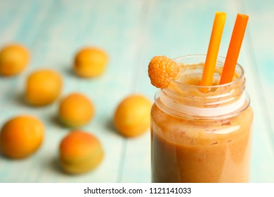 Apricot smoothies in a bottle and apricots on a wooden background.